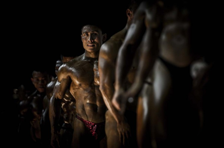 Participants compete in the 2012 International Bodybuilding and Fitness Invitation Championship in Hong Kong. Participants, who darken their skin with tanning products and apply oils to increase shine, do a series of mandatory poses and display their best shaped muscles to a panel of judges who assign points based on their appearance. (Philippe Lopez/AFP)