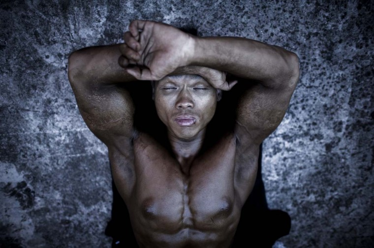 A competitor relaxes as he waits backstage during the 2012 International Bodybuilding and Fitness Invitation Championship. (Philippe Lopez/AFP)