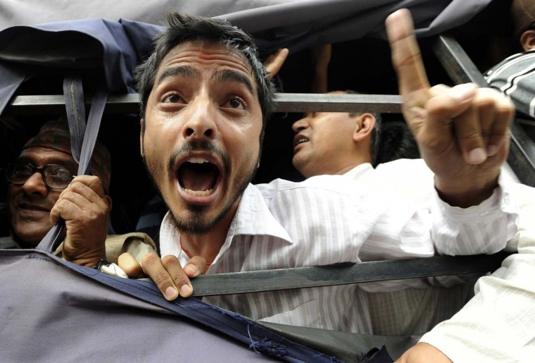 Nepalese human rights activists chant slogans from the back of a police vehicle after being arrested during a sit-in protest in front of Nepal's prime minister's residence in Kathmandu on July 18, 2012. Police arrested dozens of human rights activists who were protesting against the dissolution of constituent assembly. (Prakash Mathema/AFP/Getty Images)