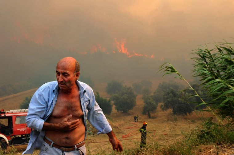 A man reacts during a wild fire near the city of Patras, some 200 kilometers southwest of Athens, on July 18, 2012. Greece's new public order minister told reporters on July 12, 2012, that one of his main concerns was effectively fighting the forest fires that plague the Mediterranean country in the summer. (Giota Korbaki/AFP/Getty Images)