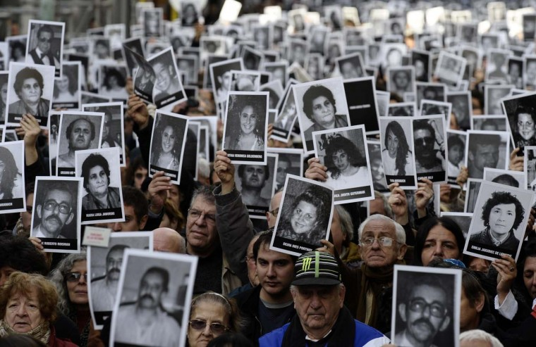 People hold portraits of victims of the terrorist bombing attack against the Argentine Israelite Mutual Association (AMIA) institute that killed 85 people and injured 300, during the commemoration of its 18th anniversary in Buenos Aires on July 18, 2012. (Alejandro Pagniale/AFP/Getty Images)