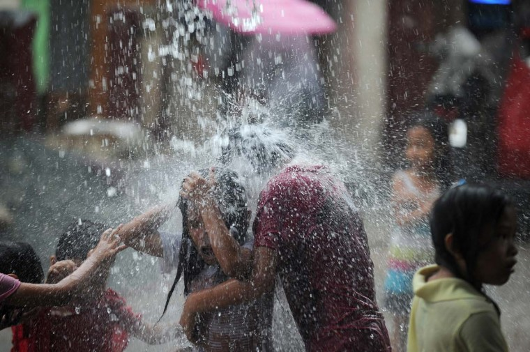 Children play in rain water pouring from an overflowing roof gutter in Manila on July 20, 2012. Classes were suspended in some parts of Metro Manila due to heavy rains caused by an area of low-pressure. (Noel Celis/AFP/Getty Images)