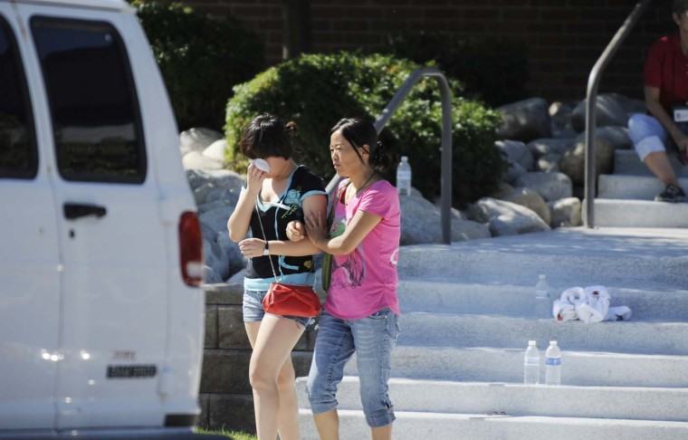 Lin Gan wipes away tears as her mother Juan Gan guides her to their car after meeting with counselors at the Gateway High School in Aurora, Colorado where families are meeting after the Century 16 theater massacre. (Jonathan Castner/AFP/Getty Images)