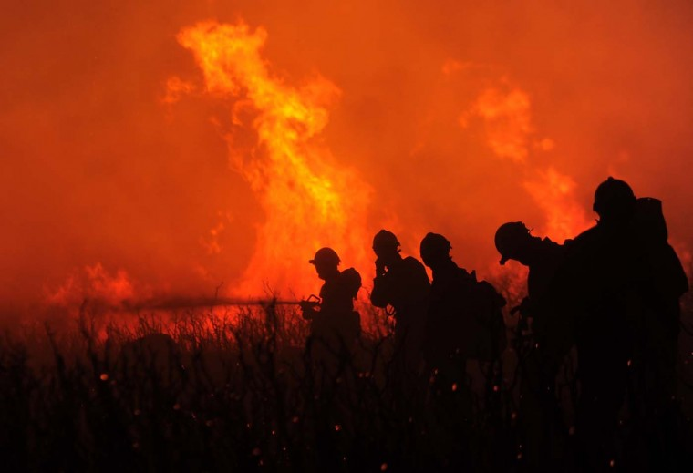 Firefighters try to extinguish a wildfire on July 23, 2012 in Ller near La Junquera (Girona), close to the Spanish-French border. (Lluis Gene/AFP/Getty Images)
