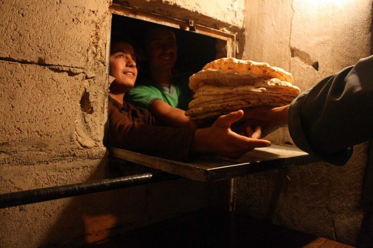 """Syrian men line up to buy bread at the only open bakery left in the city of Al-Bueda on July 23, 2012. Syrian troops were locked in fighting with armed rebels in parts of Damascus and the second city Aleppo, monitors said, as Arab nations offered President Bashar al-Assad a """"safe exit"""" if he gave up power. (Antonio Pampliega/AFP/Getty Images)"""