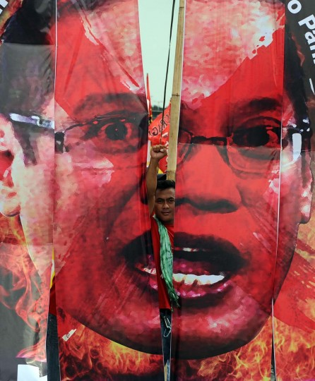 An anti-government protester raises a clinched fist next to a portrait of Philippine President Benigno Aquino during a demonstration against his state of the nation address (SONA) near the legislature building in Manila on July 23, 2012. (Ted Aljibe/AFP/Getty Images)