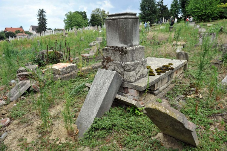 Several broken gravestones lay on the grass on July 22, 2012 in the local Jewish cemetery of Kaposvar, about 200 km south-west from Budapest as 57 graves were desecrated by vandals. (Stringer/AFP/Getty Images)