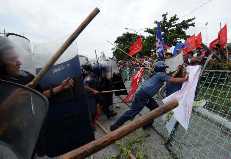 """Anti-government protesters clash with police during a demonstration against the state of the nation address (SONA) of Philippine President Benigno Aquino near the legislature building in Manila on July 23, 2012. Aquino was to deliver his annual """"state of the nation"""" speech to Congress on July 23, with legislators hoping he will tackle an escalating South China Sea dispute. (Ted Aljibe/AFP/Getty Images)"""