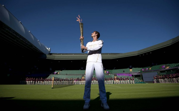 LONDON, UNITED KINGDOM -JULY 23: British tennis player Andy Murray carries the Olympic Torch in Centre Court at the Olympic tennis venue in the All England Tennis Club in Wimbledon, southwest London, on July 23, 2012. (Ben Stansall/AFP/Getty Images)