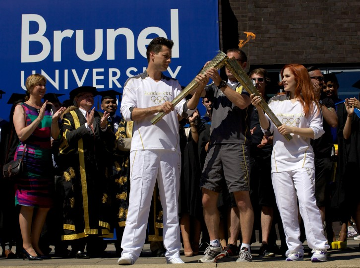 LONDON, UNITED KINGDOM - JULY 24: British music producer Mark Ronson (L) passes the Olympic flame to British singer Katy B during a torch relay at the Brunel University, on July 24, 2012 in London, three days before the opening of the London 2012 Olympic games. (Andrew Cowie/AFP/Getty Images)