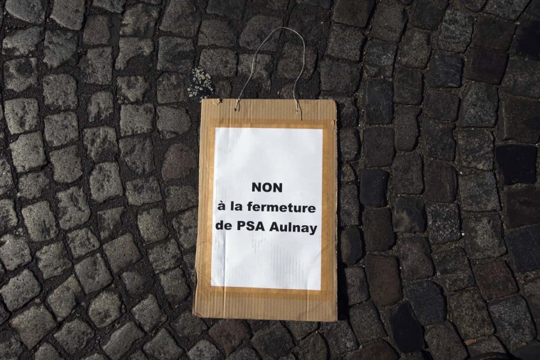 "A placard reading ""No to the closing of PSA Aulnay plant"", is pictured on the ground during a French car maker Peugeot PSA employees and unions demonstration against the planned layoffs and plant closing at Avenue de la Grande Armee, near the PSA headquarters, on July 25, 2012 in Paris. (Joel Saget/AFP/Getty Images)"