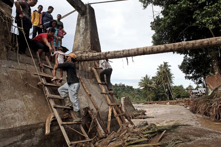 Residents cross a destroyed bridge after a flash flood hit Padang, the capital of West Sumatra province on July 25, 2012. Residents were breaking their fast while observing Ramadan on July 24 when floodwaters burst from the river banks following heavy rains, sending people fleeing and damaging hundreds of houses. (Zulki Fli/AFP/GettyImages):