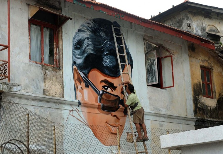 "Indian artist Ranjit Dahiya works on a mural of late actor Rajesh Khanna on a roadside building wall in Mumbai on July 25, 2012. Khanna, popularly known as the ""first superstar"" of Bollywood and the Hindi film industry's biggest heart-throb in his day, died on July 18 after months of illness. He was 69. (Punity Paranjpe/AFP/Getty Images)"