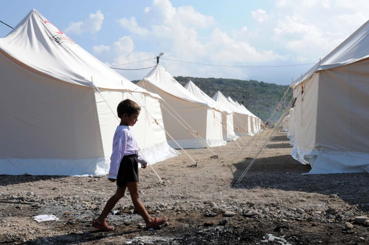 A Roma boy walks past new tents in a refugee camp near Montenegrin capital Podgorica on July 25, 2012. Some 800 Kosovo Roma, including children, were left homeless after a fire tore through a refugee camp on the outskirts of the capital, officials said. (Savo Prelevic/AFP/Getty Images)
