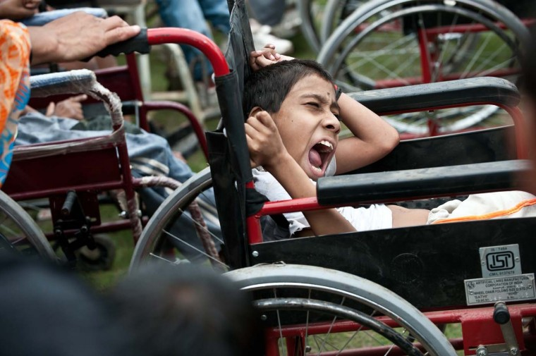 "An Indian disabled child suffering from the effects of the 1984 Bhopal disaster, reacts in discomfort while waiting to participate in a march during a ""Special Olympics"" in Bhopal on July 26, 2012. Disabled children suffering the effects of the 1984 Bhopal disaster in India will take part in the ""Special Olympics"" to protest against London 2012 sponsor Dow Chemical. The event is aimed at raising awareness about the legacy of birth defects and pollution from the accident at a factory owned by U.S. chemical company Union Carbide, which was bought by Dow in 1999, organisers said. (Prakash Singh/AFP/Getty Images)"