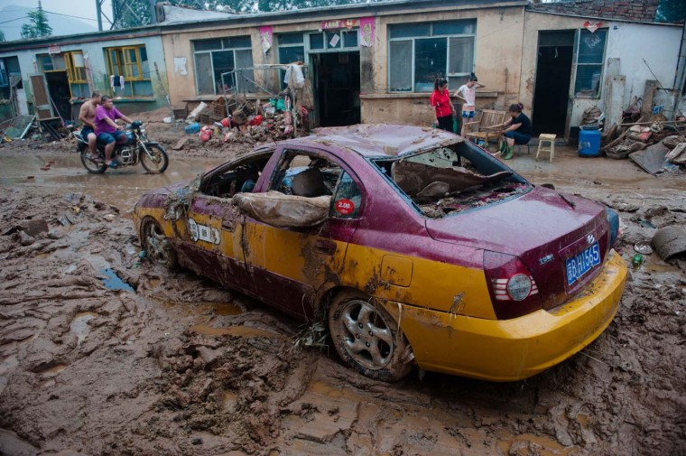 "A damaged taxi lies on a street in the devasted area in Beijing on July 26, 2012, after the worst rainstorms in six decades pounded the capital city on July 21. The flood left tens of thousands of people stranded in surging waters. Authorities in Beijing said they would begin to ""strike"" out at online critics of the government response to recent record flooding, while declining again to release updated casualty tolls. (AFP/Getty Images)"