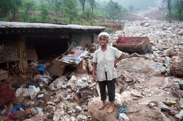 An elderly woman stands by her damaged home in the devasted area in Beijing on July 26, 2012, after the worst rainstorms in six decades pounded the capital city on July 21 leaving the metropolis flooded and tens of thousands of people stranded in surging waters. (AFP/Getty Images)