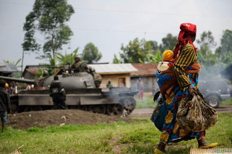 A displaced Congolese lady and her child walk past a retreating government army tank in the village of Rugari, around 37km from Goma, following an alleged ambush by M23 rebels in the Democratic Republic of the Congo's restive North Kivu province on July 26, 2012. This area has seen heavy fighting over the past three days, displacing thousands of people and increasing fears of a move by M23 on the provincial capital. (Phil Moore/AFP/Getty Images)