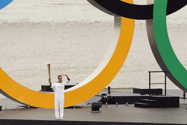 LONDON, UNITED KINGDOM - JULY 27: Amber Charles stands by giant Olympic rings mounted on a barge floating on the River Thames in front of the Tower Bridge during the 2012 London Olympic Games Torch Relay on July 27, 2012 in London. (Will Oliver Justin Tallis/AFP/Getty Images)