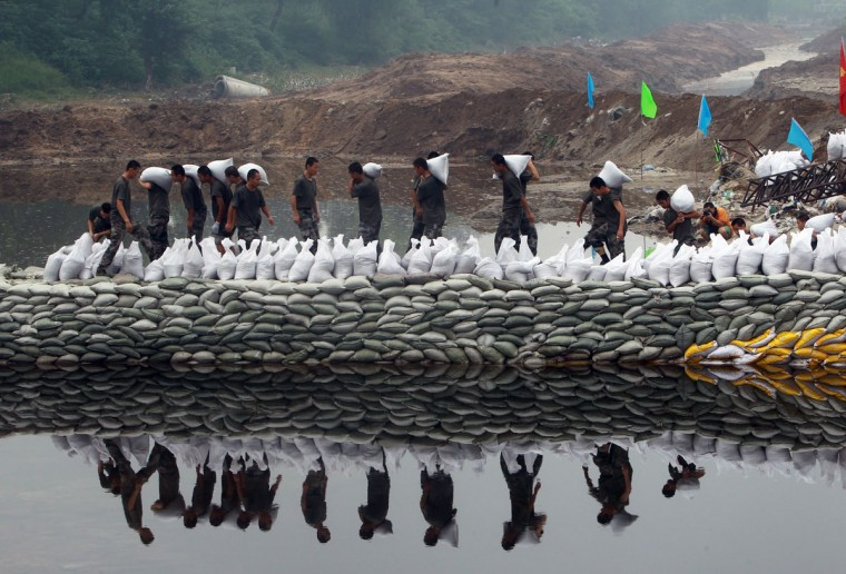 Rescuers pile sandbags along a riverbank to prevent another flooding in the worst-hit area of Fangshan, on Beijing's mountainous southwestern outskirts July 26, 2012. Distraught residents have been reporting cars being swept away and have said many people are still missing. The death toll from the worst rains to hit Beijing in more than 60 years has risen to 77, China's official Xinhua news agency said, more than doubling previous figures. (STR/AFP/Getty Images)
