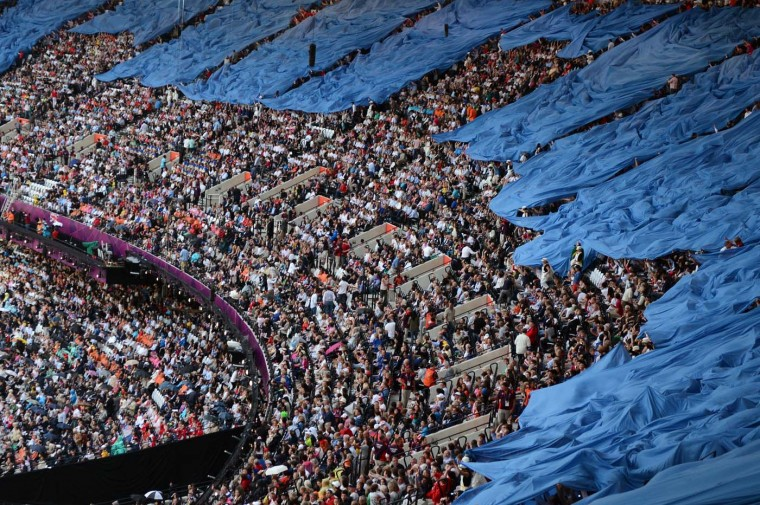 Spectators wave during the British meadow scene prior the opening ceremony of the London 2012 Olympic Games on July 27, 2012 at the Olympic stadium in London. (Franck Fife/AFP/Getty Images)