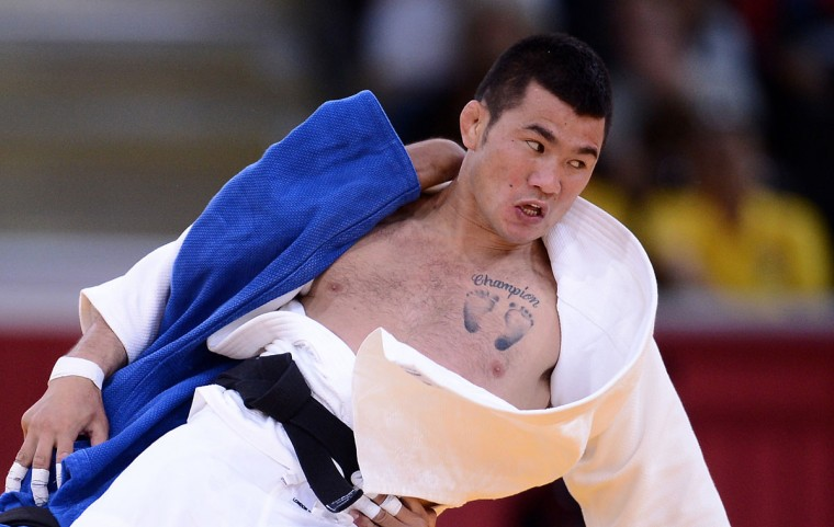 "A tattoo showing two feet and reading ""Champion"" is seen on the chest of Mongolia's Tsagaanbaatar Khashbaatar while he competes with Taiwan's Kai-Wen Tu during their men's -66kg contest match of the judo event at the London 2012 Olympic Games on July 29, 2012 at the ExCel arena in London. (Franck Fife/AFP/Getty Images)"