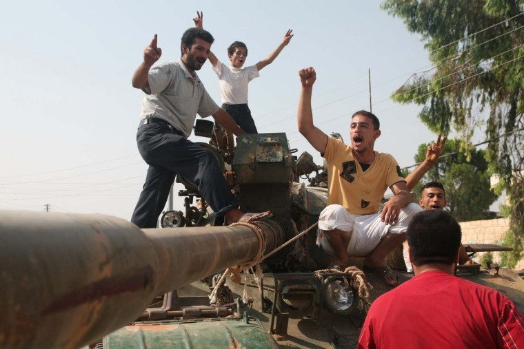 Syrian rebel fighters celebrate on top of a tank captured from the Syrian government forces at a checkpoint in the village of Anadan, about five kilometres (3.8 miles) northwest of Aleppo, on July 30 2012, after a 10-hour battle. The strategic checkpoint of Anadan secures the rebel fighters free movement between the northern city of Aleppo and Turkey, a Free Syrian Army commander and an AFP journalist said. (Iskandar Kat/AFP/Getty Images)