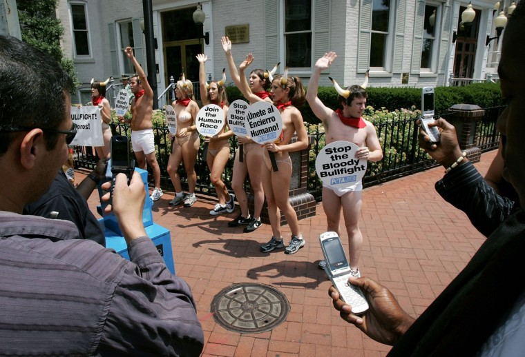 People stop to take a photograph with their mobile phones of protesters from PETA (People for the Ethical Treatment of Animals) demonstrating outside the Spanish Embassy June 21, 2005 in Washington, DC. PETA was demonstrating against the annual running of the bulls in Pamplona which they believe leads to cruel and inhumane treatment of animals.(Win McNamee/Getty Images)