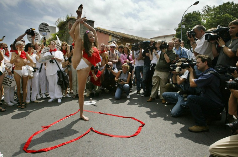 People and journalists look at a girl who does some gymnastic exercises during a march in the northern Spanish city of Pamplona 05 July 2004 to protest against bull fighting and bull run, that will be celebrated from July 7th until July 14th as part of the traditional festivities of San Fermin in Pamplona. The demonstration was organized by the pro animal and anti bullfighting association People for the Ethical Treatment of Animals (PETA). (Rafa Rivas/AFP Photo)