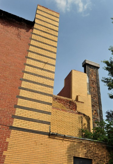 JULY 5, 2012: The north side of the former theater shows the distinctive yellow and brown brick banding, left, and the vertical neon sign, at right. The bricks wrapping around the curved north corner of the facade, seen at center of this photo, had fallen off before the fire. (Amy Davis/Baltimore Sun)