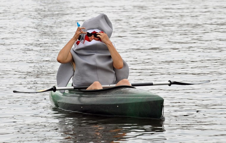 MAY 7: A kayaker serving as a safety monitor at the Canton Waterfront Park for the 2012 Baltimore Kinetic Sculpture Race, watches the race as a shark. The American Visionary Art Museum hosted the race in which amphibious, human powered vehicles race through Federal Hill, Caton and Patterson Park in a 15-mile road, water, mud and sand race course. (Kenneth K. Lam/Baltimore Sun)