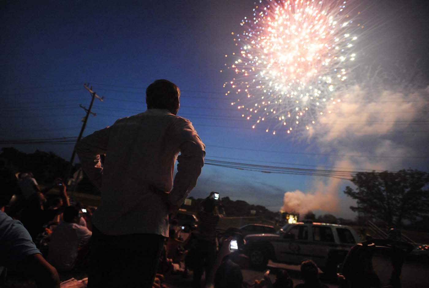 BALTIMORE, MD - JULY 04: A man stands among the crowd watching the annual fireworks show at Loch Raven Technical Academy on July 4th. (Noah Scialom for Patuxent Homestead)