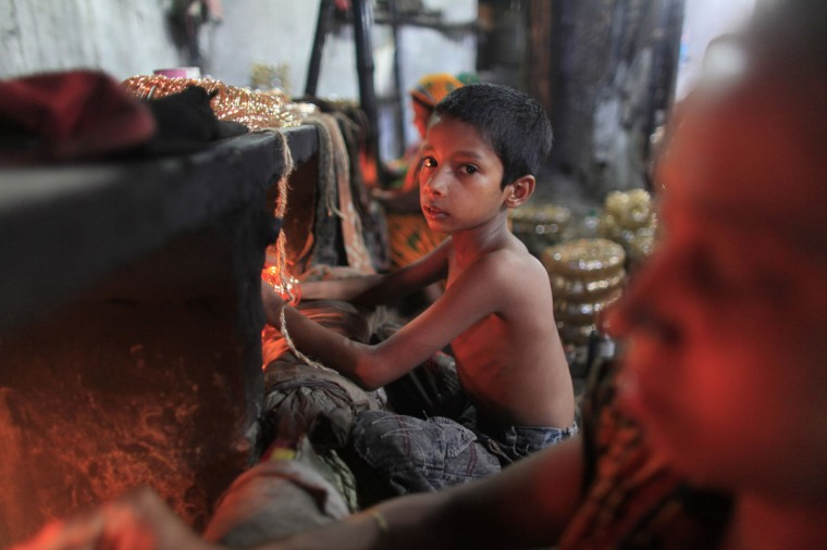 Hridoy, 7, works in front of a small kiln at a glass bangle factory in Old Dhaka. According to the management of the factory, around 150 women and children work some 15 hours a day manufacturing glass bangles. Workers earn about 500-700 takas per week ($6.25 - $8.75). (Andrew Biraj/Reuters)