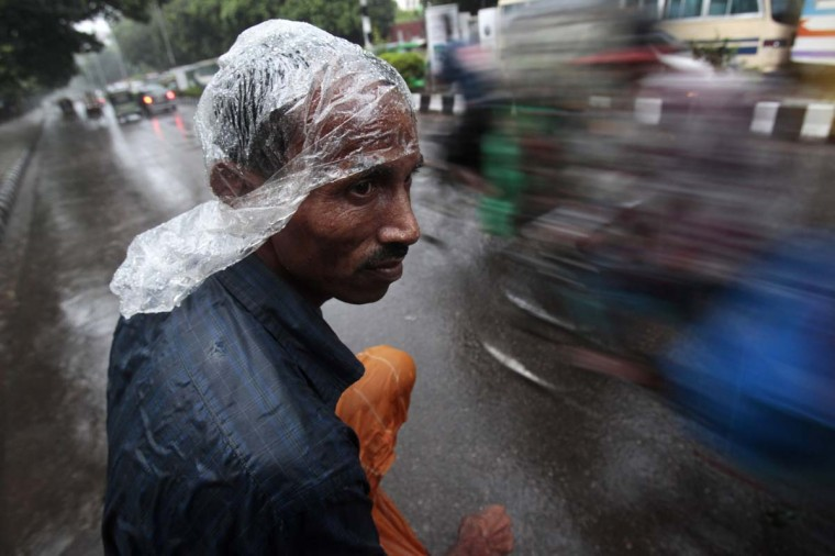 A rickshaw puller waits for passenger in the rain in Dhaka. (Andrew Biral/Getty Images)
