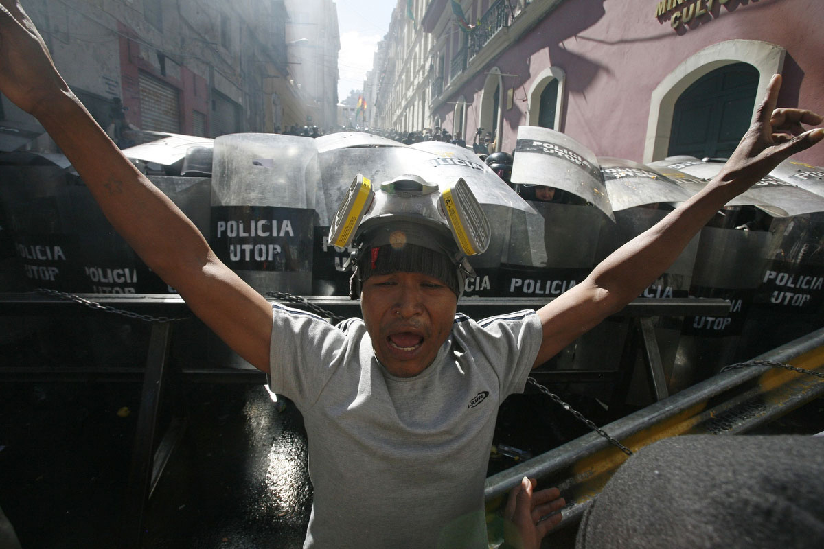 An Amazonian indigenous man protests in front of riot policemen during clashes in La Paz. The indigenous people of the territory of national park Isiboro Secure, known by its Spanish acronym TIPNIS, remain in La Paz after walking 640 km (397 miles) to defend their territory against the planned construction of a highway through the middle of the park. (Gaston Brito/Reuters)