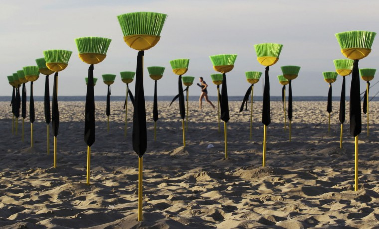 """A man runs near brooms placed by members of the Rio de Paz (Peace Rio) Non-Governmental Organization (NGO) at Copacabana beach as a form of protest in Rio de Janeiro. A total of 81 brooms, which represent the number of senators in the country, were placed at the beach to symbolize the need to """"sweep off"""" corruption in the Brazilian senate. (Sergio Moraes/Reuters)"""