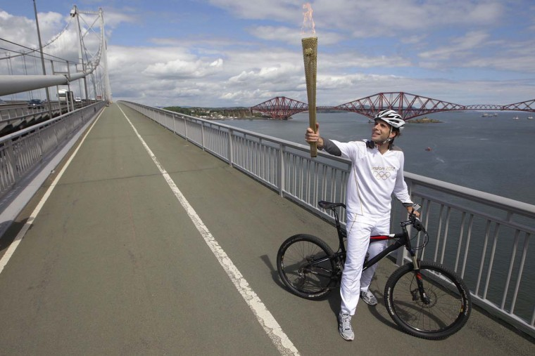 JUNE 13: British long-distance cyclist Mark Beaumont poses for photographers on the Forth Road Bridge while carrying a London 2012 Olympic torch near South Queensferry, Scotland. (David Moir/Reuters)