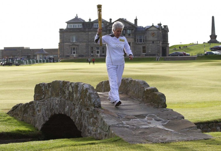 JUNE 13: Torch bearer Louise Martin carries the London 2012 Olympic torch as she runs over the Swilken Bridge next to the eighteenth tee on the Old Course at St Andrews in Scotland June 13, 2012. (David Moir/Reuters)