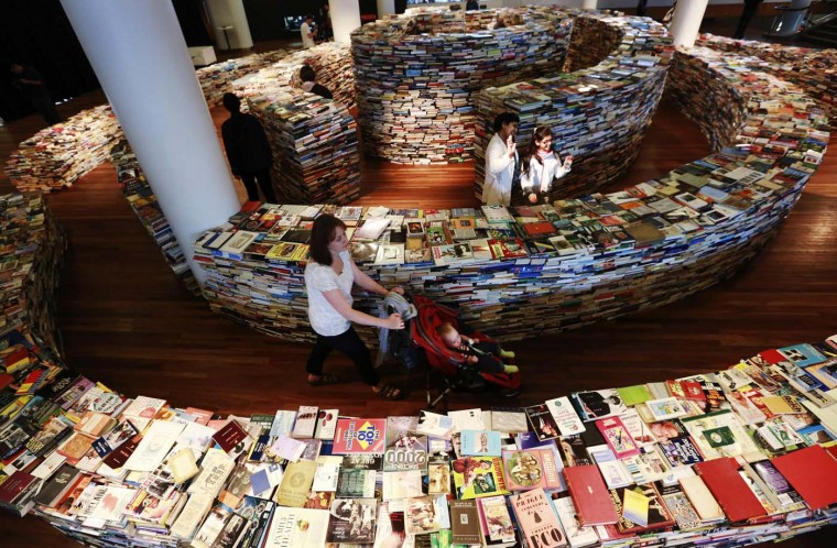 """Visitors walk in a labyrinth installation made up of 250,000 books titled """"aMAZEme"""" by Marcos Saboya and Gualter Pupo at the Royal Festival Hall in central London July 31, 2012. (Olivia Harris/Reuters)"""