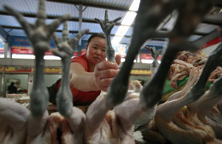 A vendor holds a chicken foot as she displays it for sale at a market in Huaibei, Anhui province, July 9, 2012. China's annual consumer inflation cooled to 2.2 percent in June, from May's 3.0 percent, official data showed on Monday, giving Beijing more scope to ease monetary policy. (Stringer/Reuters)