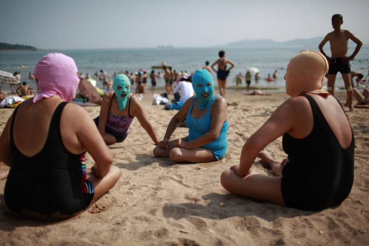 Women, wearing nylon masks, chat as they rest on the shore during their visit to a beach in Qingdao, Shandong province July 6, 2012. The mask, which was invented by a woman about seven years ago, is used to block the sun's rays. The mask is under mass production and is on sale at local swimwear stores. (Aly Song/Reuters)
