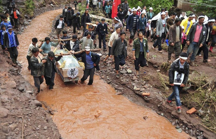 Villagers carry the coffin and portrait of a victim who was killed by a flash flood as they wade through a stream during a funeral in Sujia village of Zhaotong, Yunnan province. (Wong Campion/Reuters photo)