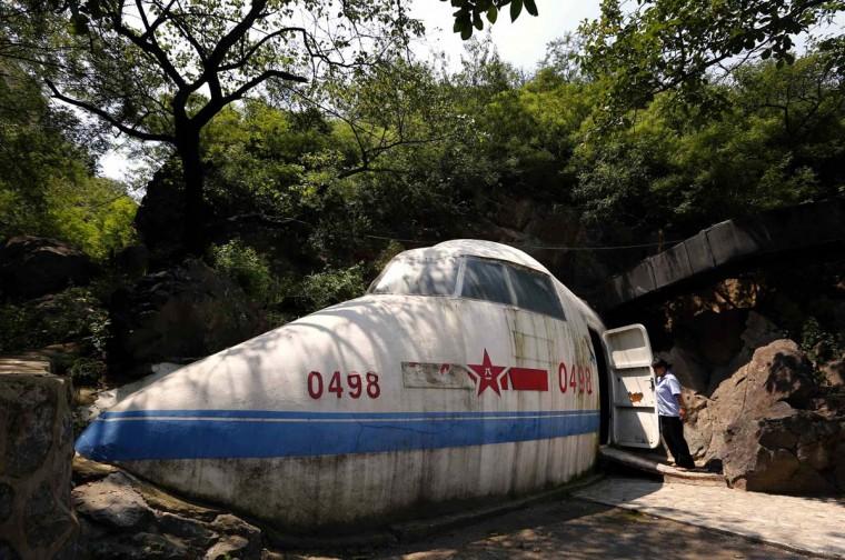 Shaped in the form of an aeroplane, an attendant opens the door to the entrance of a cave that was once the headquarters of former Chinese Communist military leader Lin Biao, located in mountains on the outskirts of Beijing. (David Gray/Reuters photo)