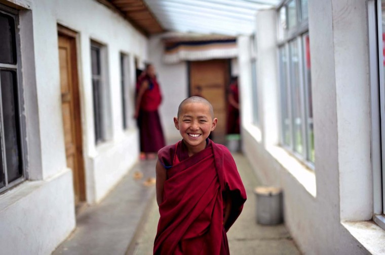 A young Tibetan monk laughs as he waits for a free medical examination at a hospital in Henan Autonomous County, Qinghai province. (Reuters photo)