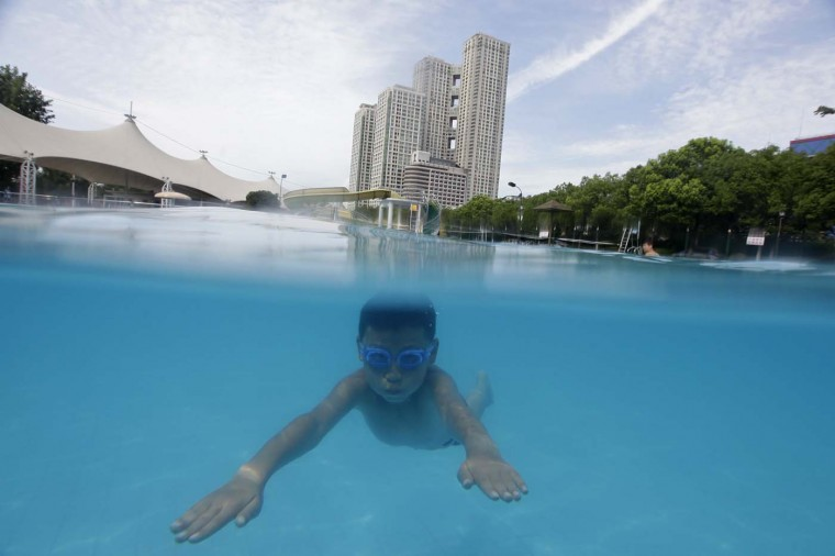 A boy plays in a swimming pool at the Jiangtan park, near the Yangtze River in Wuhan July 8, 2012. (Stringer/Reuters)