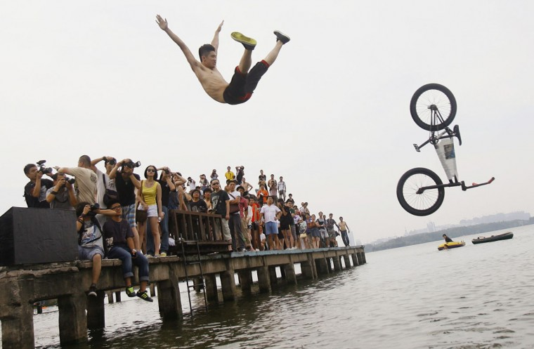 An extreme cycling enthusiast performs a stunt with a bicycle during a diving activity at the East Lake in Wuhan, Hubei province. This activity, which is held by local netizens, attracts many extreme cycling enthusiasts to take part, local media reported. Picture taken July 9, 2012. (China Daily/Reuters)