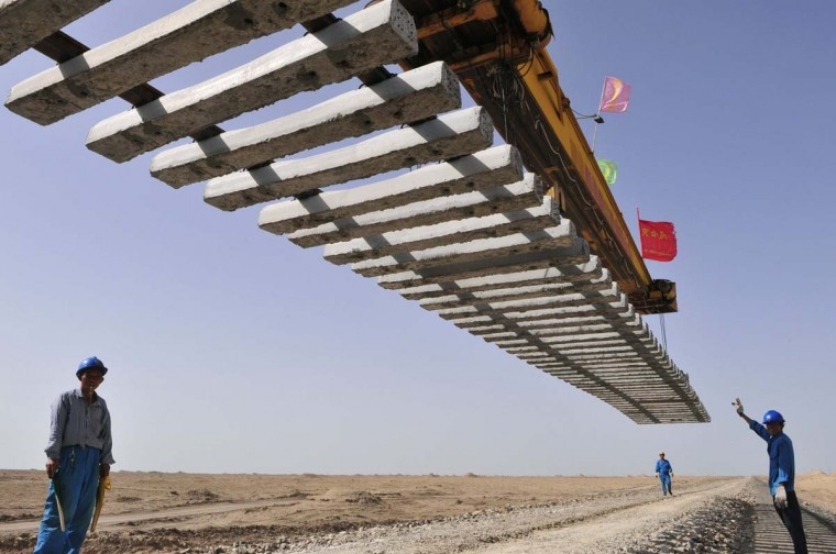Workers direct a crane to lay a segment of tracks on the Kumul-Lop Nor line's railway bed in Lop Nor, Xinjiang Uighur Autonomous Region. The line, which is the first going to Lop Nor, is estimated to be completed on July 20, 2012, local media reported. (Rooney Chen/Reuters photo)