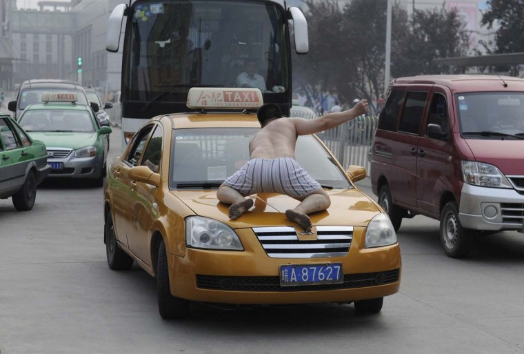 A topless man smashes the windshield of a taxi in the middle of a street in Hefei, Anhui province July 17, 2012. The man ran onto a busy street on Tuesday morning wearing only a pair of shorts, climbing onto cars and smashing windows with his bare fists. He was taken away to the hospital by policeman and doctors after smashing nearly 20 vehicles in half an hour. Police said there was no identification with the man, and he would go through psychiatric examination to determine whether he was mentally ill, local media reported. (Stringer/Reuters)
