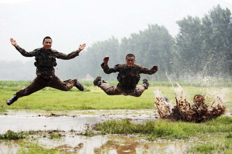 Soldiers jump as they take part during a military training session in muddy water at a military base in Jinan, Shandong province, July 23, 2012. (China Daily/Reuters)