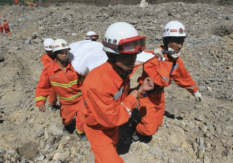 Rescuers carry a body of a victim after a landslide hit an iron ore mine in Xinyuan county of Kazak Autonomous Prefecture of Ili, Xinjiang Uighur Autonomous Region July 31, 2012. Seven people have been confirmed dead while around 21 remained missing after a mudslide hit northwest China's Xinjiang Uighur autonomous region Tuesday morning, the local government said, Xinhua News Agency reported. (China Daily/Reuters)